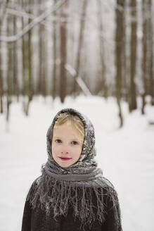 Portrait of little girl wearing headscarf standing in front of winter forest - EYAF00505