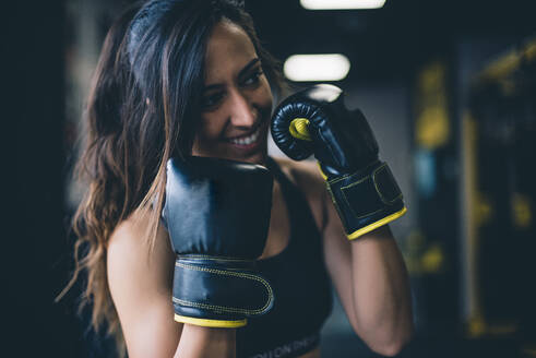 Smiling female boxer in a gym - CJMF00028