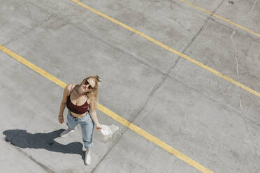 Young woman standing on a car park - LHPF01003