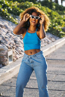 Portrait of laughing young woman with sunglasses - MPPF00052