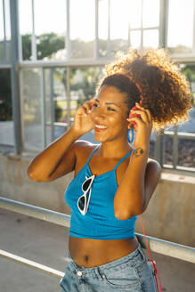 Portrait of smiling young woman listening music with headphones - MPPF00061