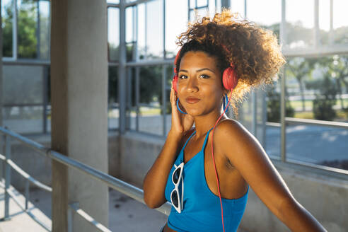 Portrait of smiling young woman listening music with headphones - MPPF00064