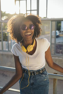 Portrait of laughing young woman with sunglasses and headphones - MPPF00073