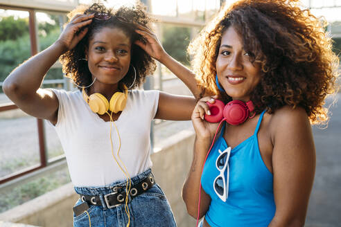 Portrait of two happy young women  with headphones at evening twilight - MPPF00079