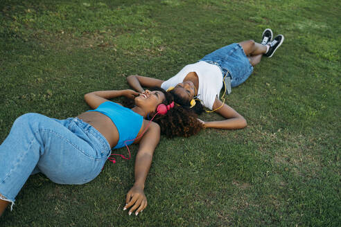Two young women relaxing on meadow listening music with headphones - MPPF00085