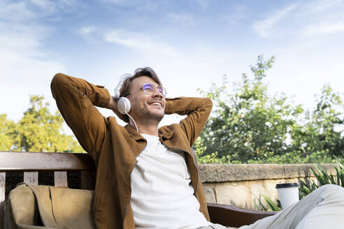 Laughing man sitting on bench listening music with headphones - AFVF04032