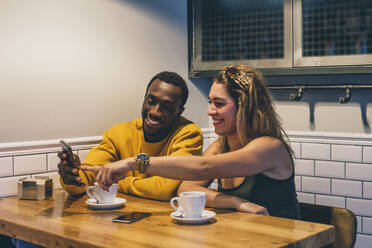 Portrait of smiling couple in a coffee shop using smartphone - CJMF00041