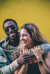 Portrait of happy couple in front of yellow wall - CJMF00050
