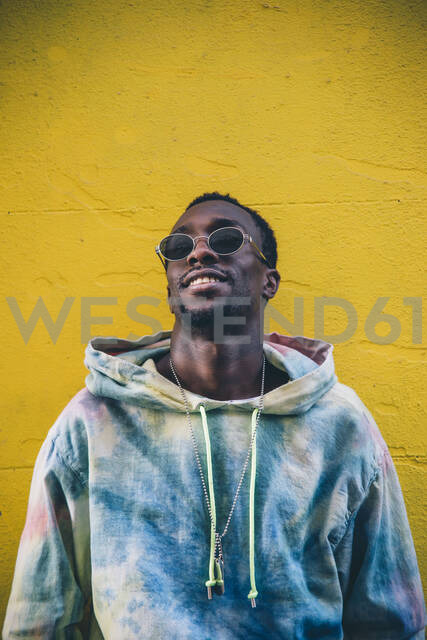 Portrait of young man wearing sunglasses leaning against yelow wall - CJMF00053 - Jesús Martinez/Westend61