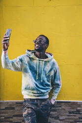 Portrait of smiling young man taking selfie with smartphone in front of yellow wall - CJMF00056