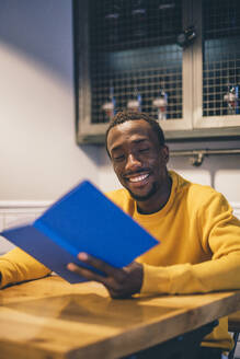 Portrait of smiling man in a coffee shop reading a book - CJMF00062