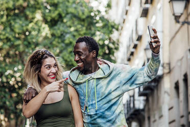 Portrait of laughing couple taking selfie with smartphone, Madrid, Spain - CJMF00065