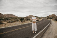 Woman standing on road showing her bra, Joshua Tree National Park, California, USA - LHPF01009