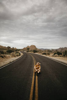 Woman sitting on road, Joshua Tree National Park, California, USA - LHPF01012
