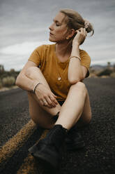 Woman sitting on road, Joshua Tree National Park, California, USA - LHPF01015