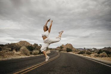 Woman jumping on road, Joshua Tree National Park, California, USA - LHPF01018