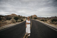 Woman standing on road, Joshua Tree National Park, California, USA - LHPF01021