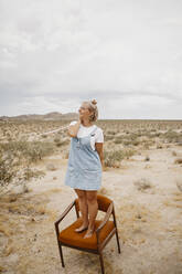 Woman standing on a chair in desert landscape, Joshua Tree National Park, California, USA - LHPF01048