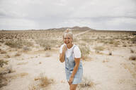 Portrait of laughing young woman in desert landscape, Joshua Tree National Park, California, USA - LHPF01054