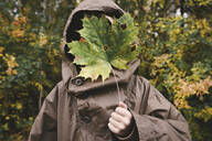 Boy wearing brown rain coat hiding his face behind autumnal maple leaf - EYAF00510