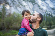 Portrait of happy baby girl kissed by her father, Yosemite National Park, California, USA - GEMF03204