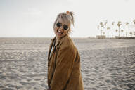 Happy young woman on the beach, Venice Beach, California, USA - LHPF01059