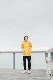 Young woman wearing yellow rain coat - NAF00119