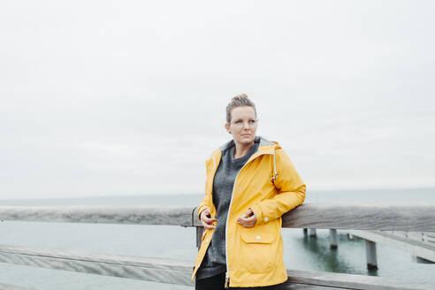 Young woman wearing yellow rain coat - NAF00122
