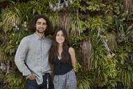 Portrait of smiling young couple in front of plant wall - SUF00595