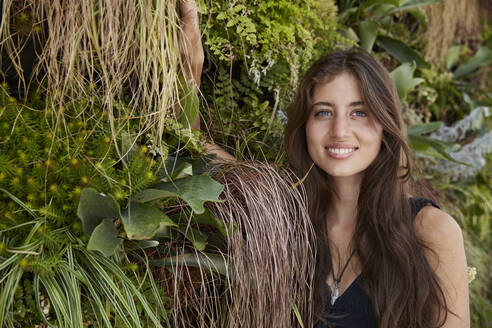 Portrait of smiling young woman in front of plant wall - SUF00601