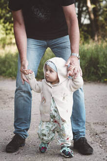 Little girl making her first steps with her grandfather - EYAF00529