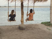 Back view of two women sitting on swings at seafront, Gili Islands, Bali - KNTF03638