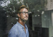 Casual young businessman behind windowpane in office - PNEF02080