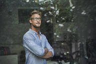 Casual young businessman behind windowpane in office - PNEF02083