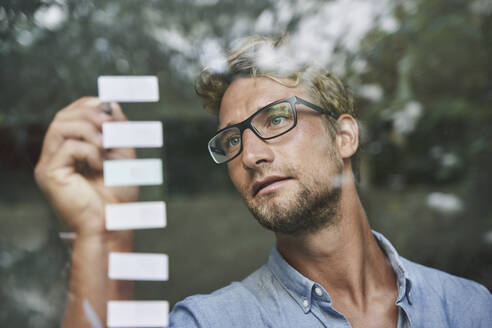 Casual young businessman with adhesive notes behind windowpane in office - PNEF02086