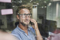 Casual young businessman on the phone behind windowpane in office - PNEF02089