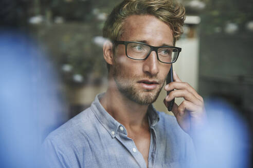 Casual young businessman on the phone behind windowpane in office - PNEF02092
