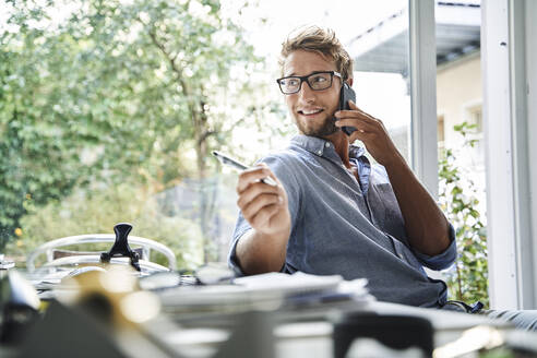 Casual young businessman on the phone at desk in office - PNEF02095