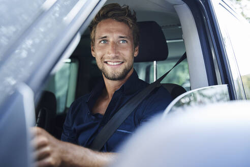 Smiling young man in car - PNEF02098