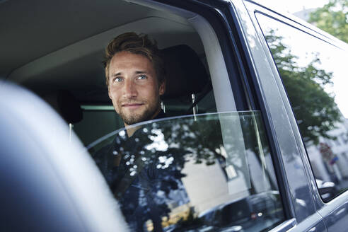 Portrait of confident young man in car - PNEF02101