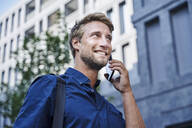 Smiling young businessman on the phone in the city - PNEF02116