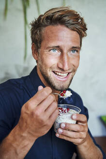 Portrait of smiling young man eating muesli - PNEF02140