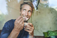 Portrait of smiling young man eating muesli - PNEF02143
