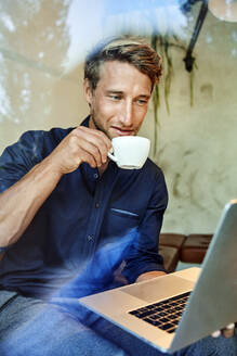 Young businessman drinking coffee and using laptop in a cafe - PNEF02146