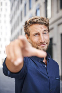 Portrait of confident young man in the city pointing his finger - PNEF02161