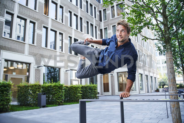 Young man jumping over railing in the city - PNEF02164 - Philipp Nemenz/Westend61