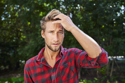 Portrait of young man wearing checkered shirt outdoors - PNEF02167