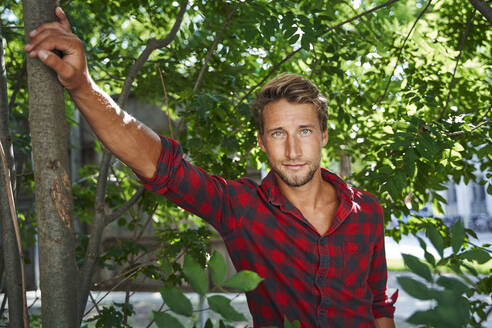 Portrait of confident young man wearing checkered shirt leaning against a tree - PNEF02170