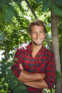 Portrait of smiling young man wearing checkered shirt leaning against a tree - PNEF02173
