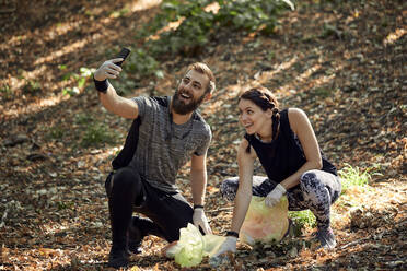 Couple taking a selfie during plogging in forest - ZEDF02620